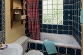 A blue tiled bathroom with large tub and window