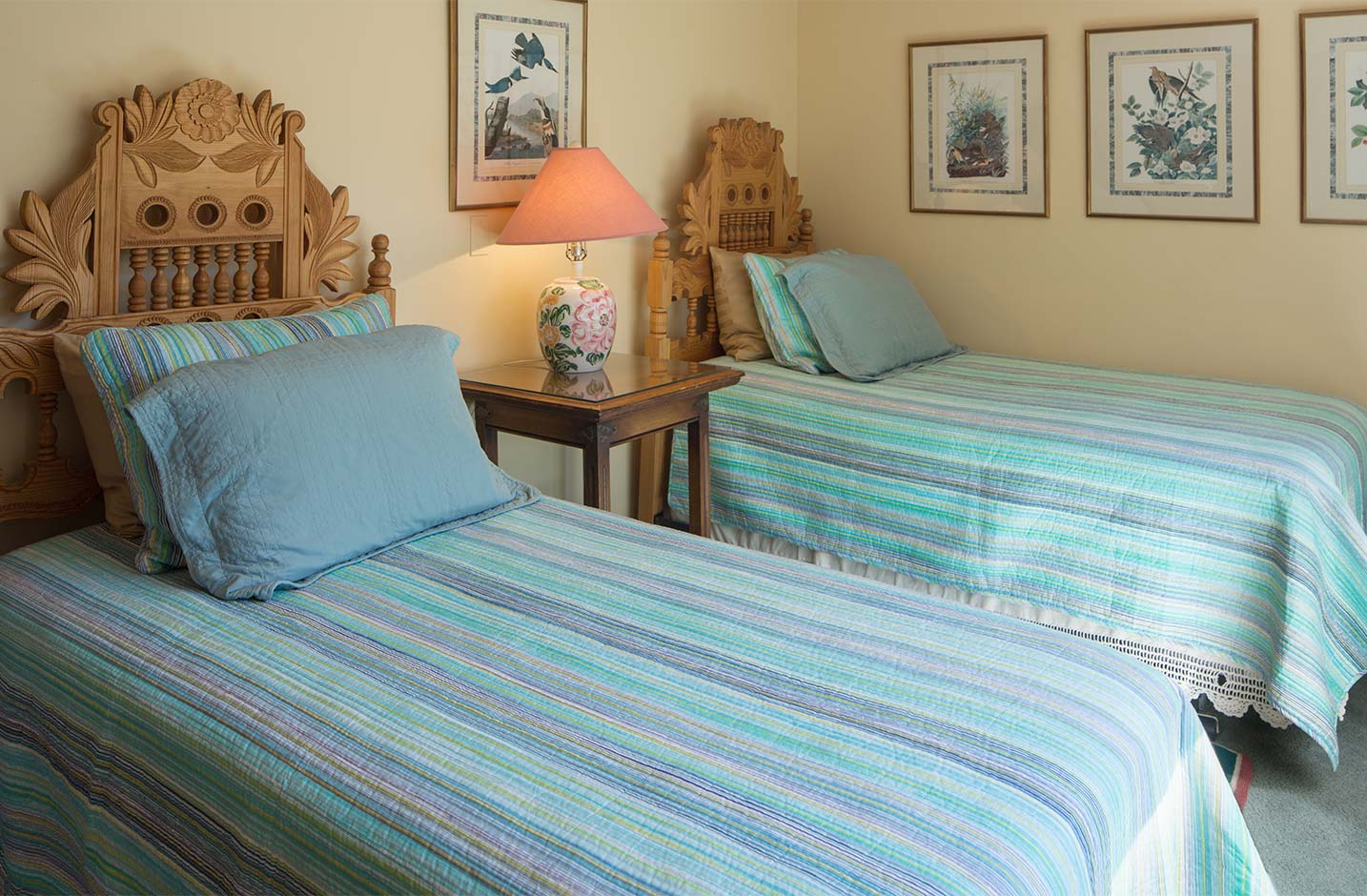 A room with two twin beds and matching teal bed spreads