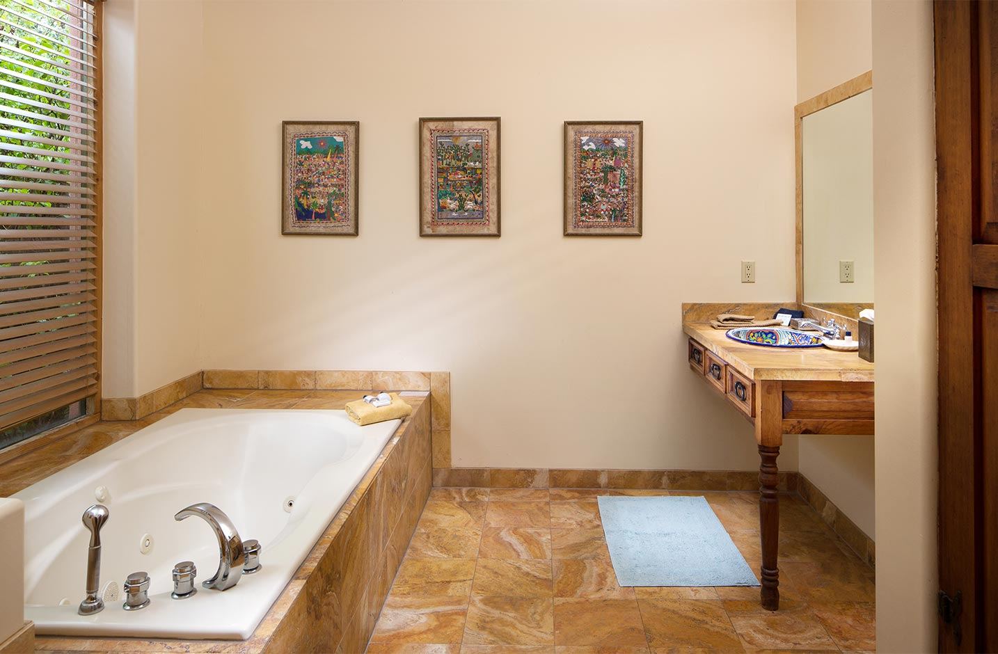 A large soaking tub with a mirror and sink