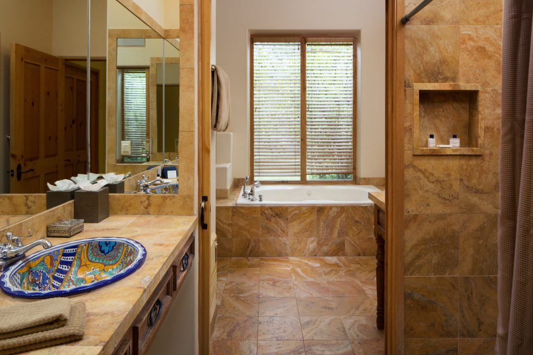 Bathroom with sinks, walk-in shower, and a soaking tub