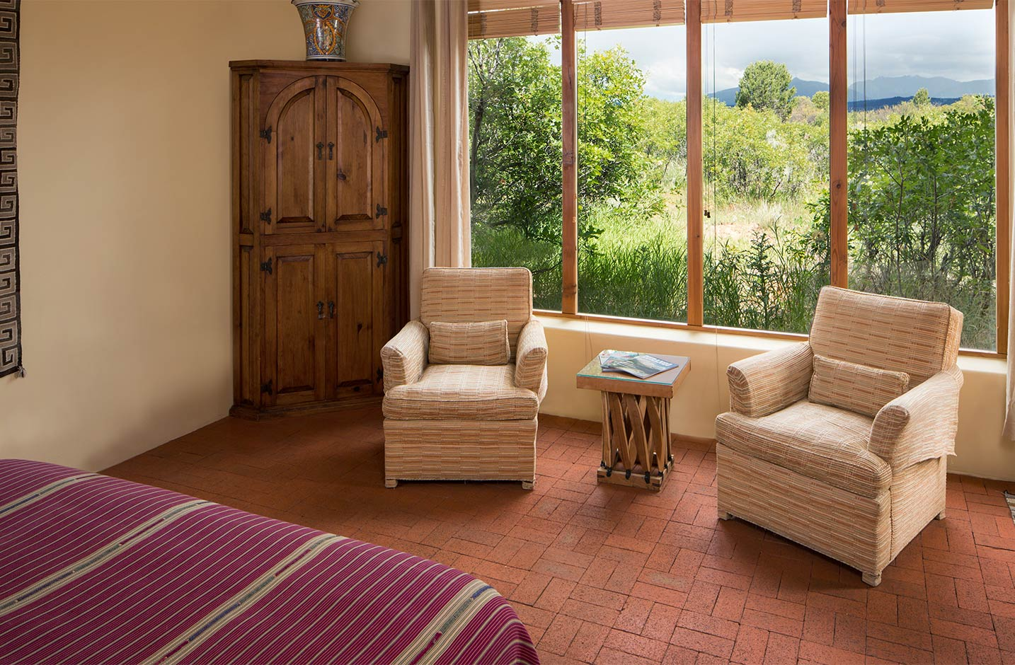 A seating area in the bedroom with large windows