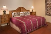 A king size bed with wooden headboard in a large room