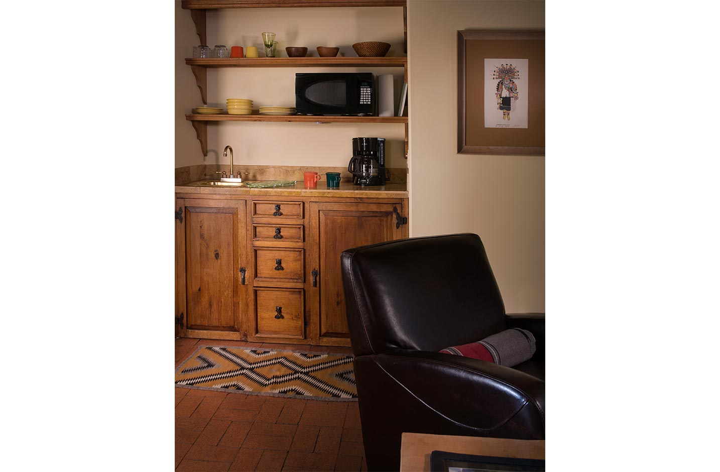 A chair at a writing desk and a wetbar with microwave and coffee maker