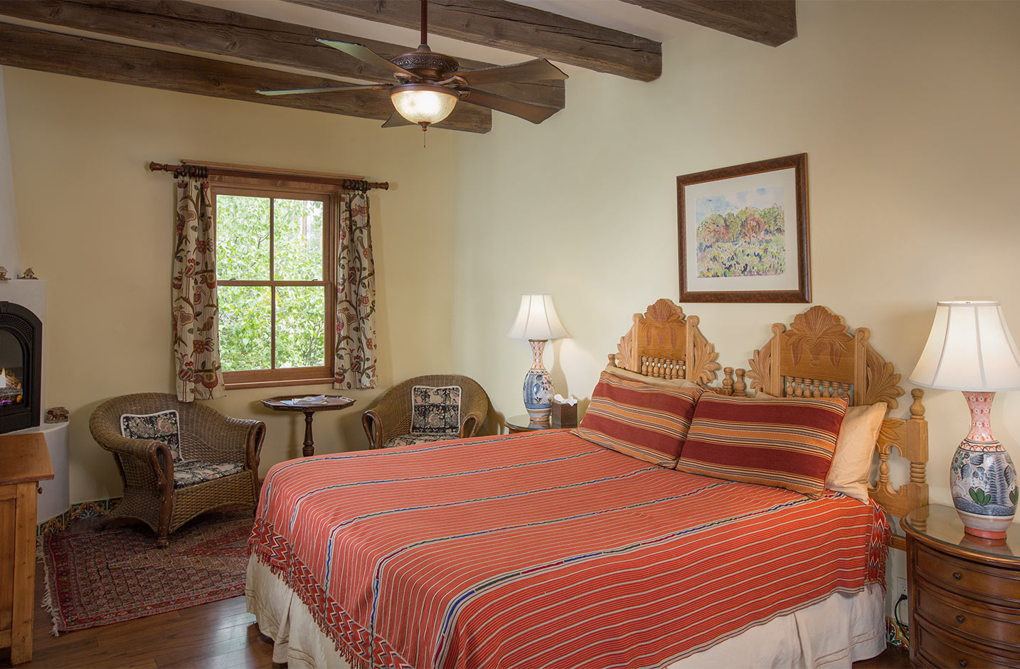 Room with a king size bed, ceiling fan, gas fireplace, and seating area