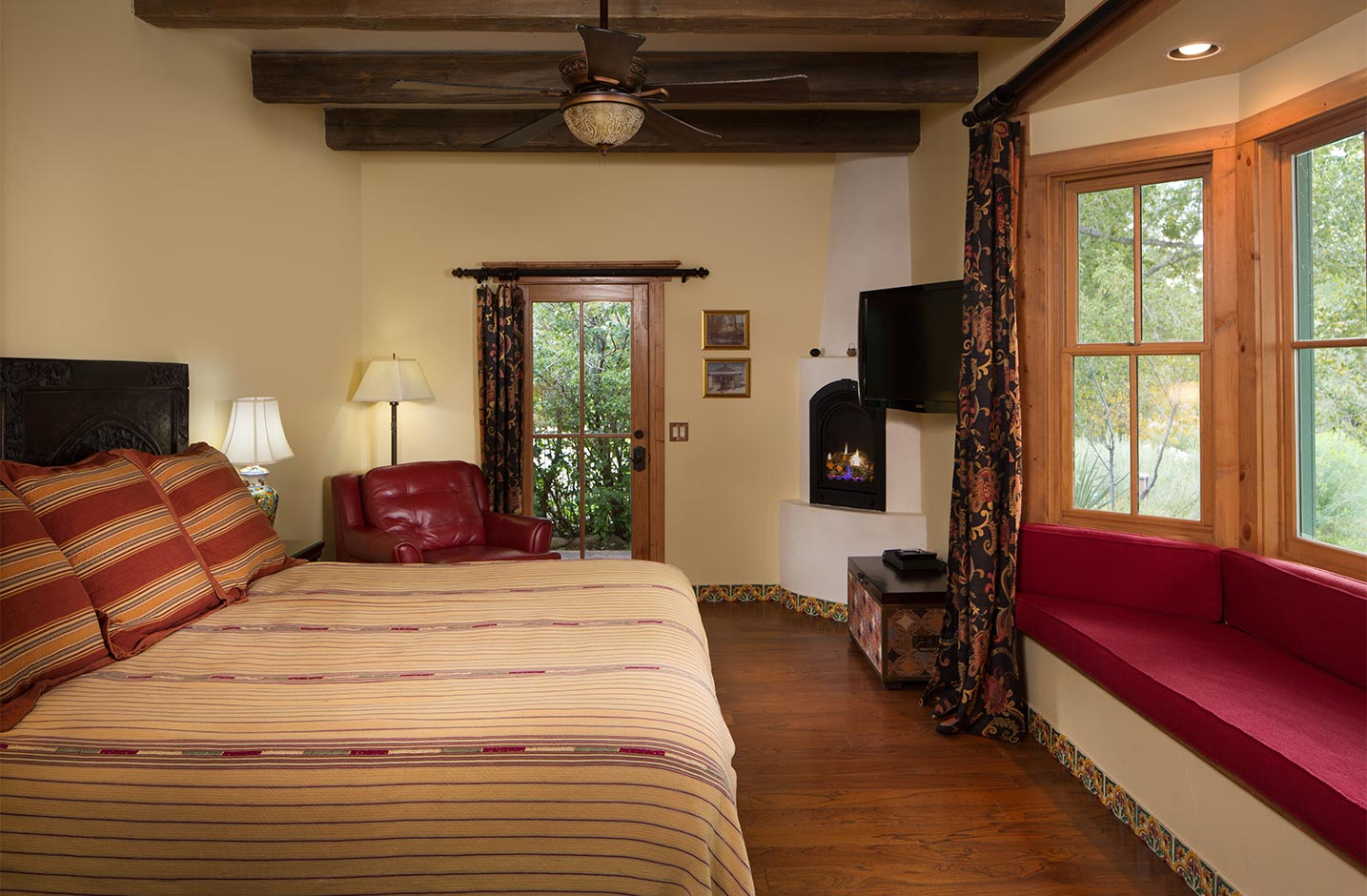 Room with a king size bed, ceiling fan, gas fireplace, a recessed seating area, and door to the outside