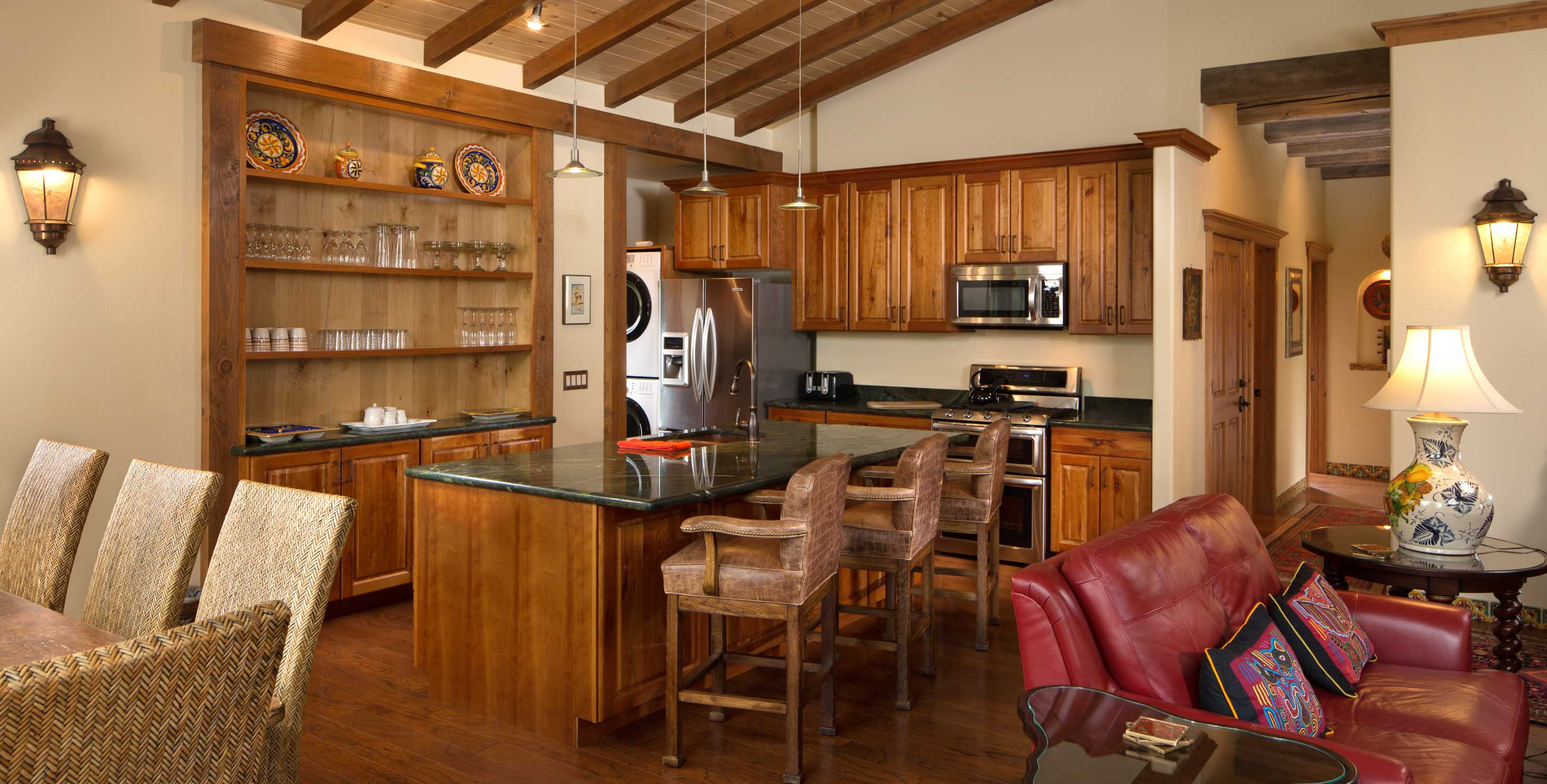 Large kitchen with island and bar stools, dining area, and red couch
