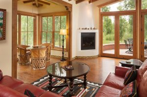Large living room with leather couch, double doors to the outside patio, and natural light