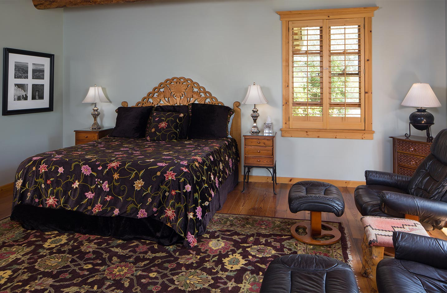 A queen bed in a spacious room with a seating area
