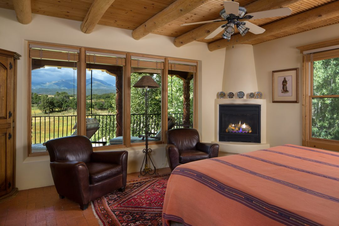 Bedroom with king bed, fireplace, ceiling fan and big windows with scenic views