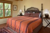 A king size bed with wooden headboard and two side tables with lamps