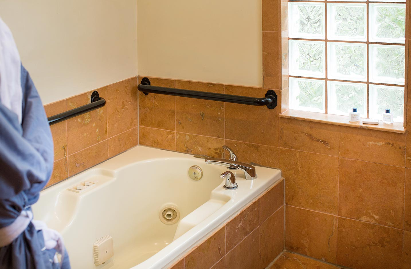 A Whirlpool tub with grab-bars and glass block windows