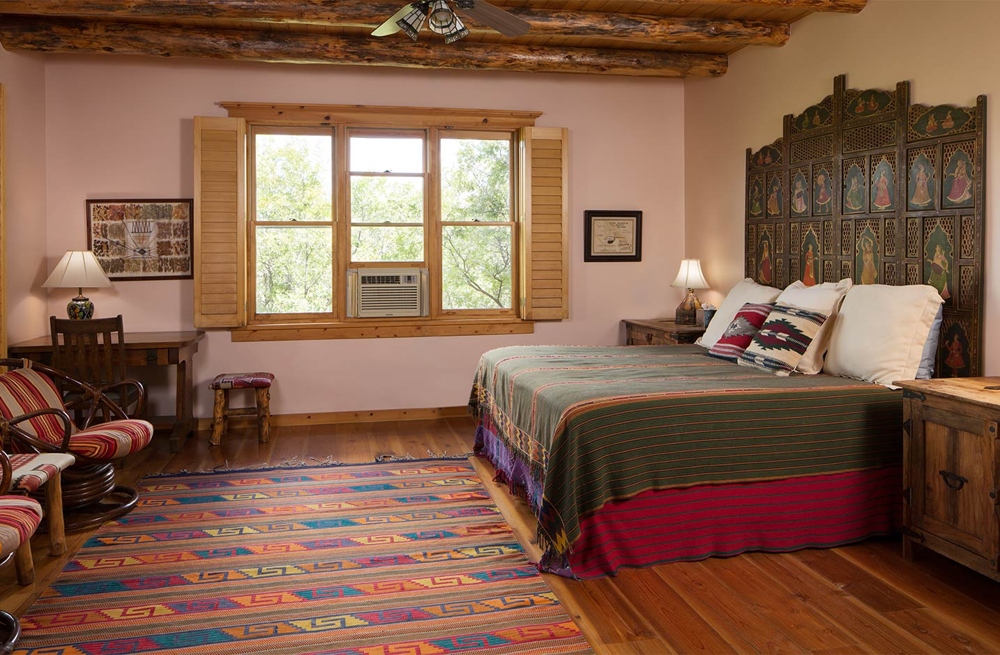 A spacious bedroom with hardwood floors and a king bed and seating area