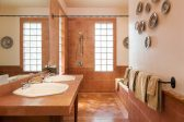Bathroom with walk-in shower, vanity sinks, and glass block wall