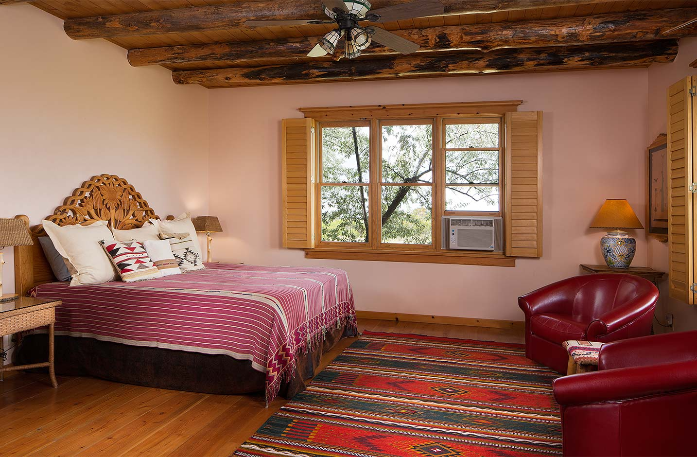 King bed in a spacious bedroom with wooden floors