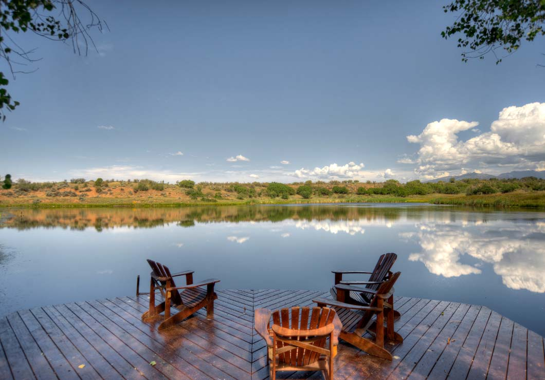 Wooden dock with three chairs overlooking a large private lake