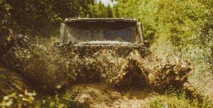 Off road Jeep splashing through a mud puddle