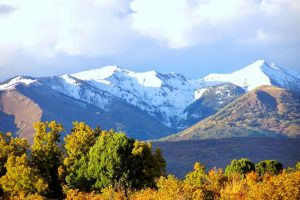 a mountain view with snow capped peaks