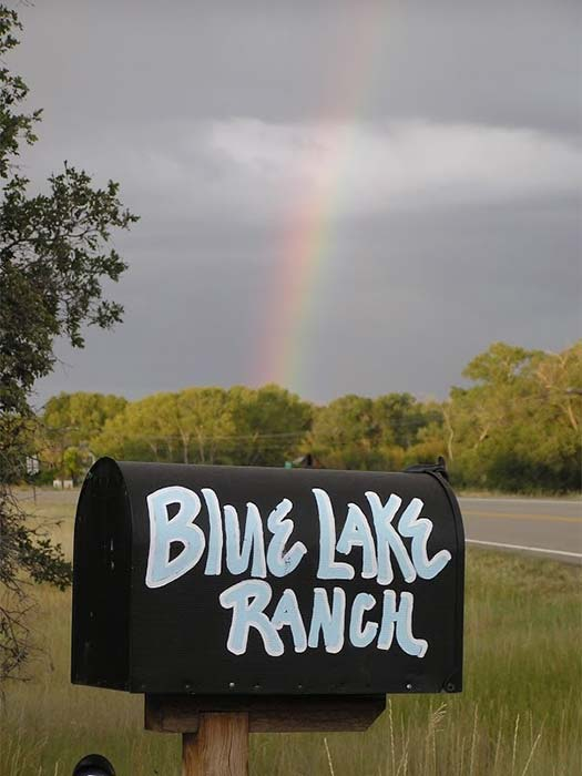 A mailbox with Blue Lake Ranch painted on it and a rainbow in the background in Durango, CO