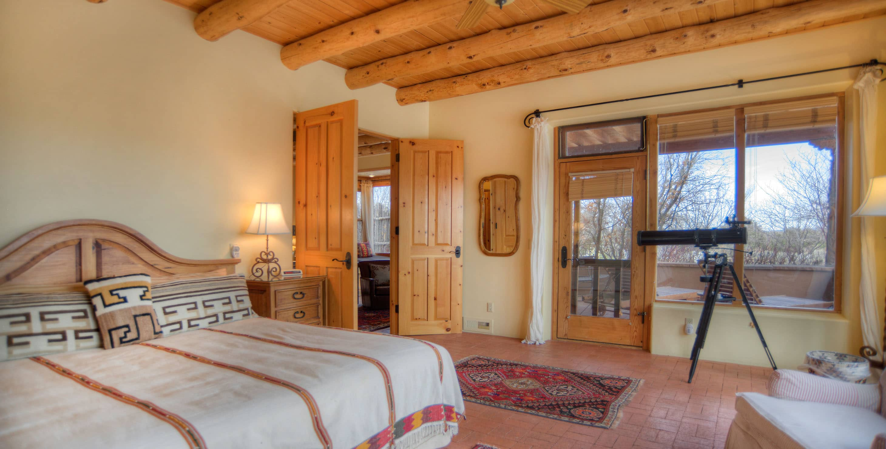 Spacious bedroom with king bed, seating area, double doors, and a doorway to a private patio