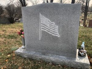 Grey granite upright headstone, engraved with american flag