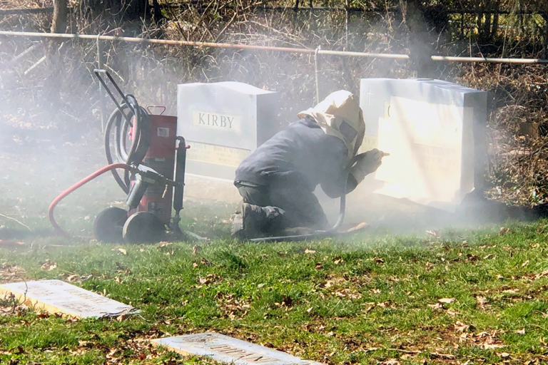 Monument Engraver sandblasting additional names and date onto an existing upright headstone in the cemetery