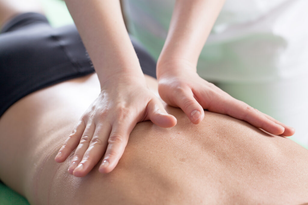 Valdosta chiropractor Marcie Kinsey Gay treating a male patient's back