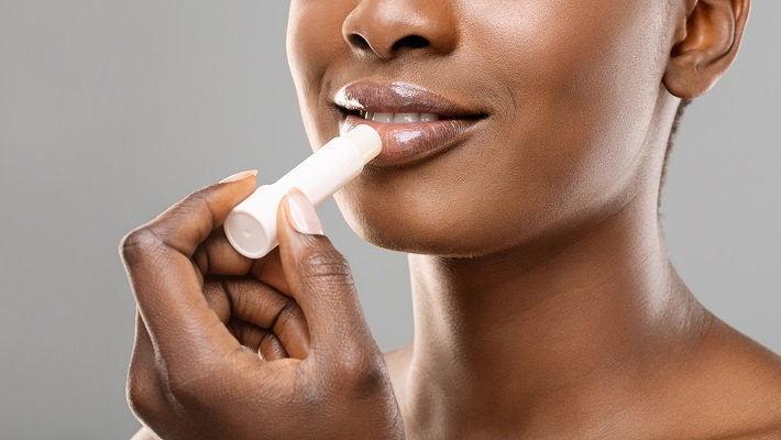 Unrecognizable woman applying hygienic balm to her plump lips over grey background, closeup