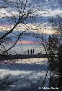 Three people silhouetted in front of a Lake Michigan sunrise