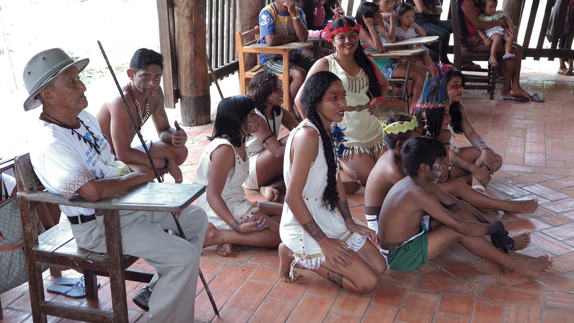 Tuxawa Donato,  a leader among the indigenous tribe, sits with Sateré Mawé youth in native dress.