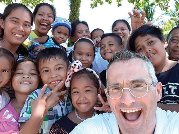 Fr. Simone Caelli, PIME Missionary, with some of the youth of his parish in the Philippines