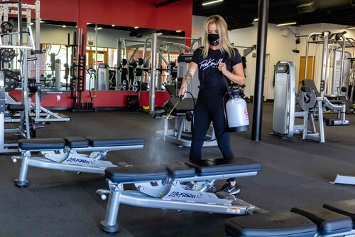 personal trainer spraying down gym benches with sanitizer after use