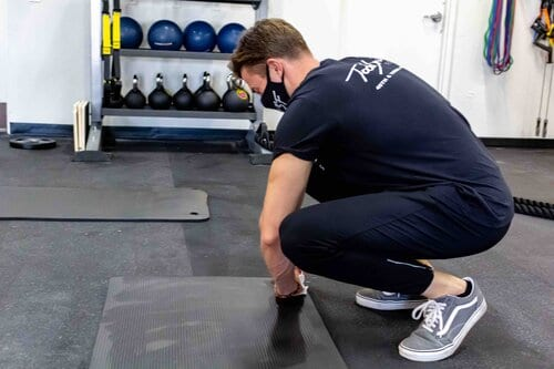 Gym employee wiping down fitness mats after use