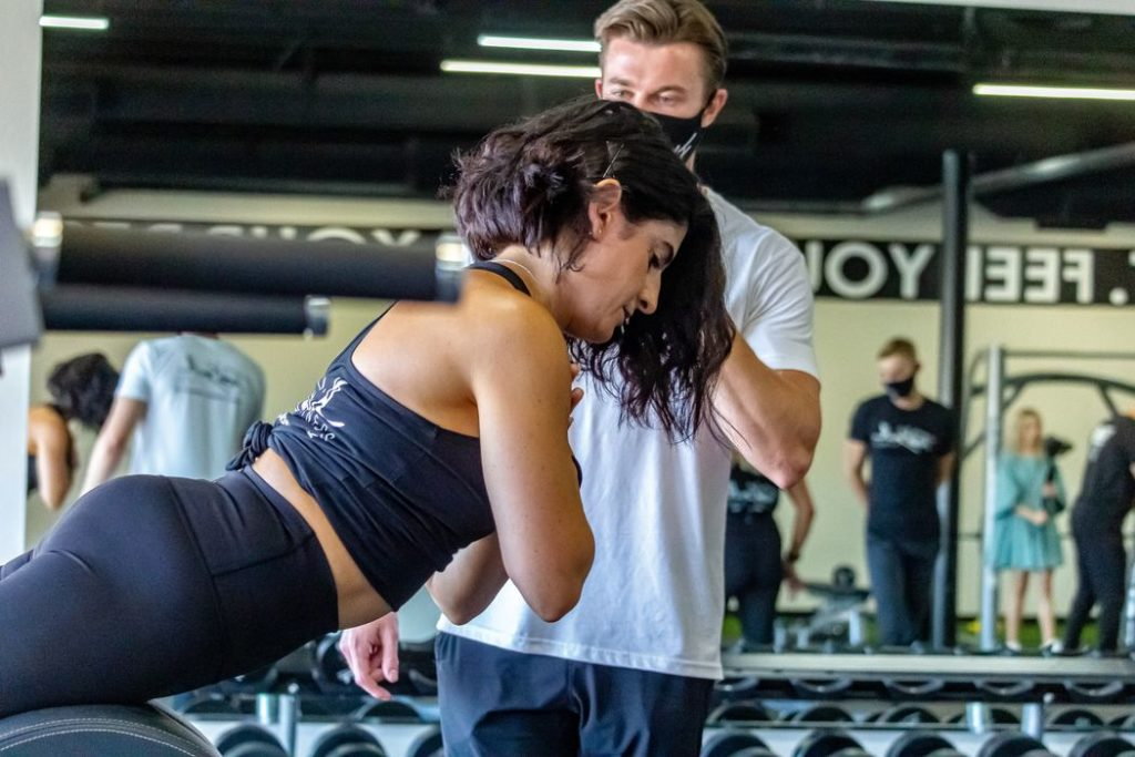 Personal trainer training gym member on glute exercises