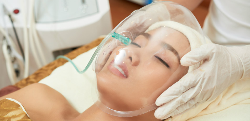 Close-up shot of relaxed Vietnamese woman lying on treatment table with closed eyes while undergoing beauty procedure at modern salon