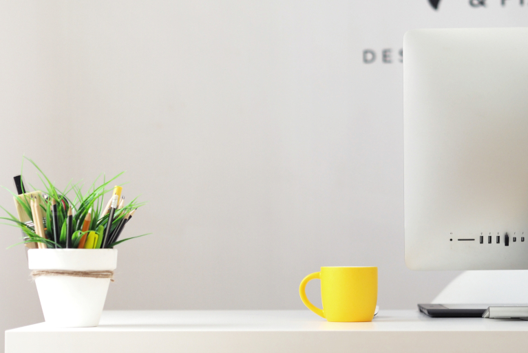 desk workspace with computer pot plant and yellow mug