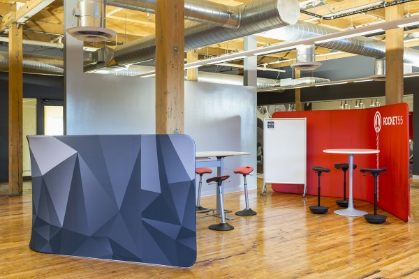 Colorful Safco room dividers, tables and ergonomic stools in office space in older building
