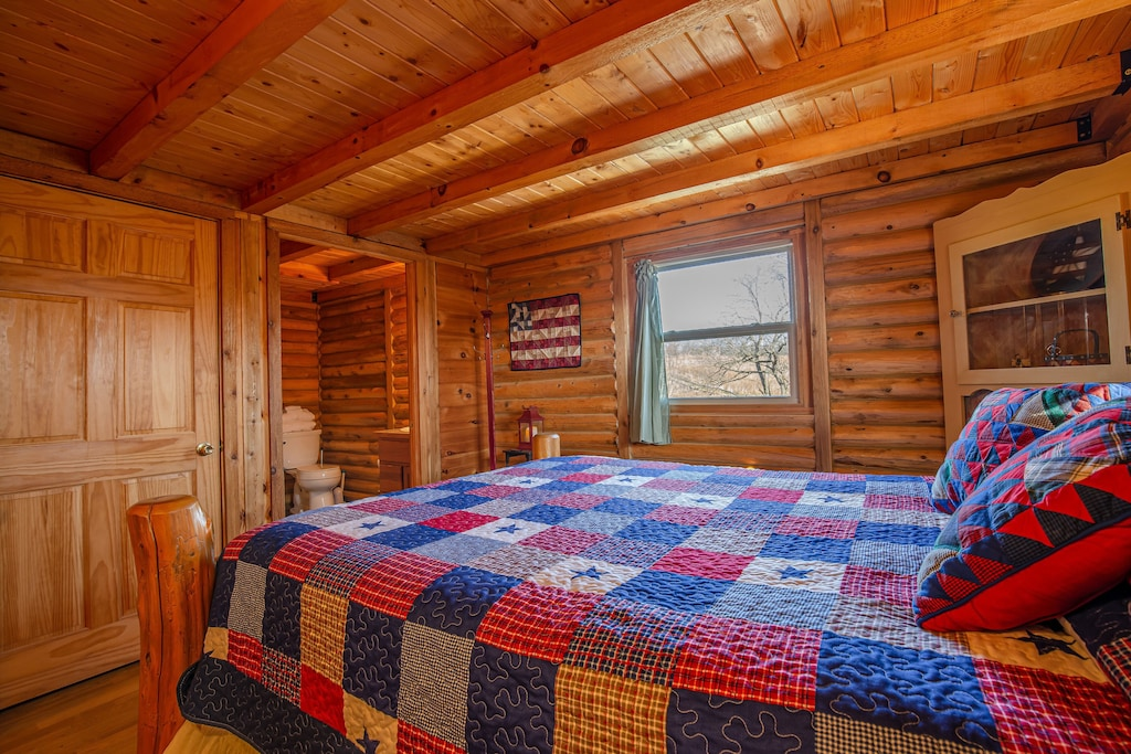 Cabin room with a bed that has red and blue sheets and pillows