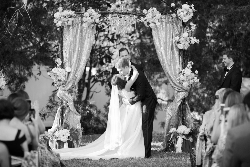 Bride & Groom Kissing at Arbor Archway Outdoor Ceremony | Travel Inspired Themed Glamorous Gold & White Wedding Luxmore Grande Estate Anna Christine Events Justin DeMutiis Photography