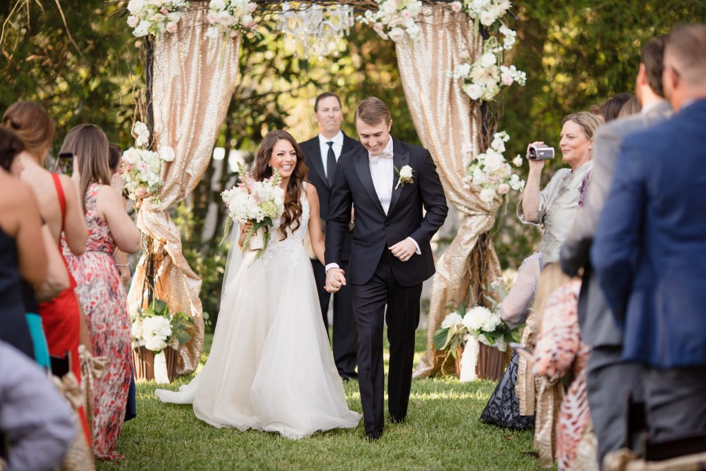 Bride & Groom Exit Outdoor Ceremony | Travel Inspired Themed Glamorous Gold & White Wedding Luxmore Grande Estate Anna Christine Events Justin DeMutiis Photography