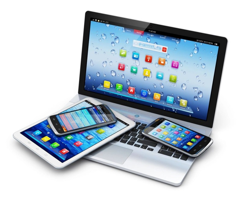 Two cellphones and a tablet placed on top of an open laptop