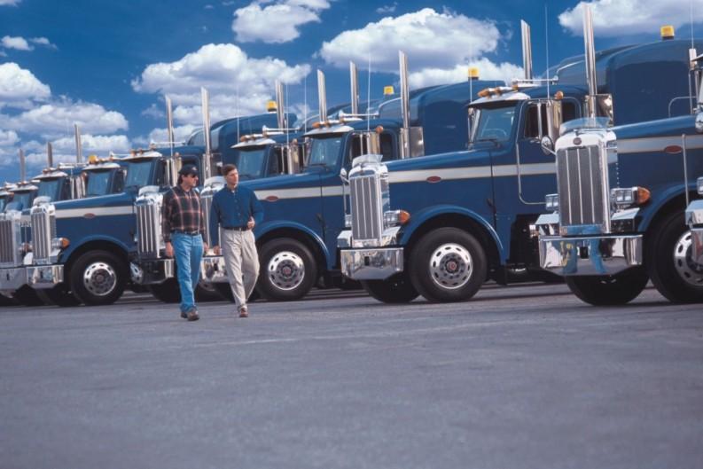 Two men walking in front of a fleet of shiny blue trucks