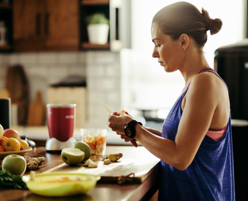 Athletic woman slicing fruit while preparing smoothie in the kitchen.