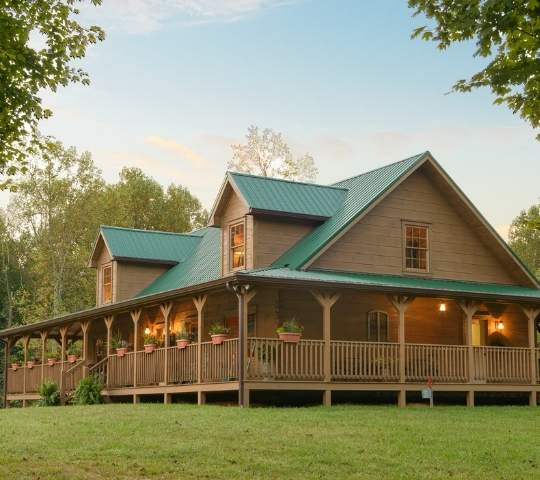 Photo of exterior of log home with wrap around porch and central home with upper loft dormers.