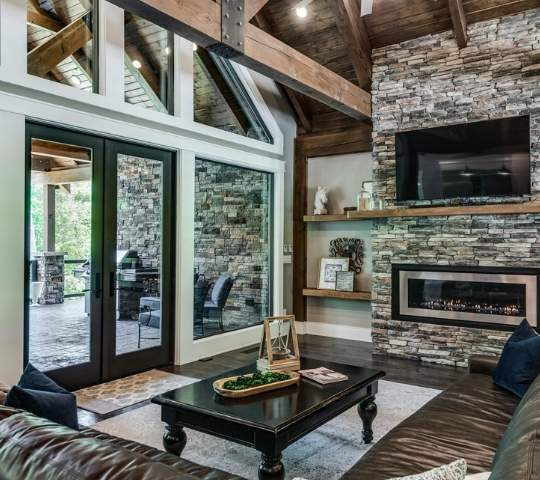 Photo of great room space with exterior wall of window and glass doors opening to extensive outdoor living space with grilling and dining area. The great room has a large gas stone fireplace, exposed wood a-frame beams and exposed wood ceiling.