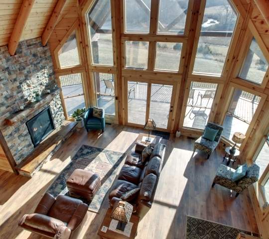 photo take from loft area of a great room of a log home with soaring two story windows, log walls and flooring with exposed log support beams.