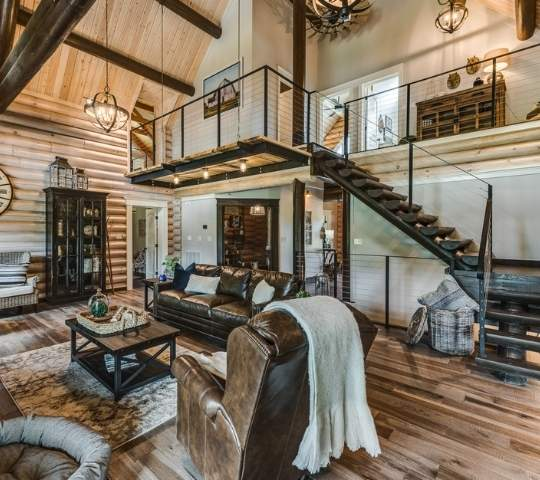 photo of great room take from lower level showing open loft, above an open staircase. The ceiling and walls are wood with matching wood hardwood flooring.