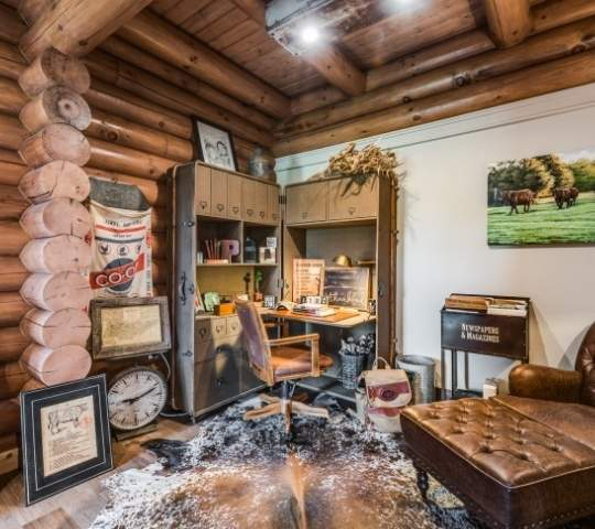 Photo of a home office built into a home with exposed round log chink style walls and exposed wood ceiling
