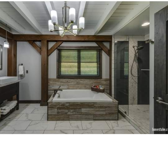 Photo of a contemporary soaker tub and walk in shower with stone flooring and painted wood ceiling