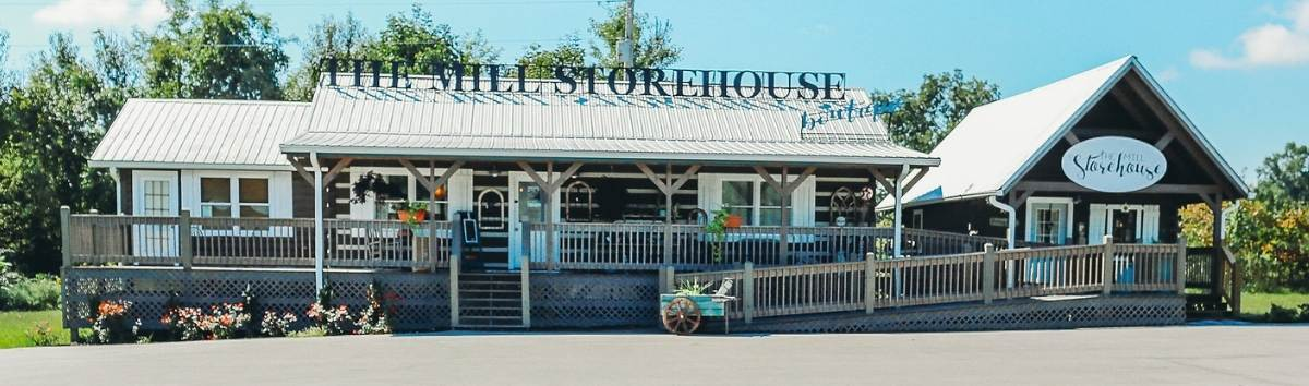 Photo of The Mill Storehouse with a metal roof and chink style dark logs. A long porch extends to a separate smaller building that houses a specialty shop.