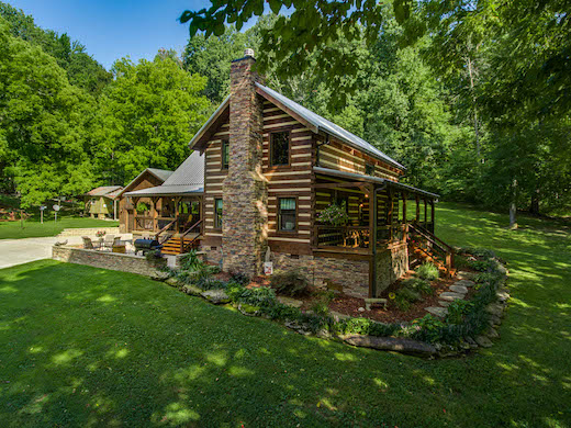 Photo of traditional two stroy log home with expansive front and back porches, chink log style